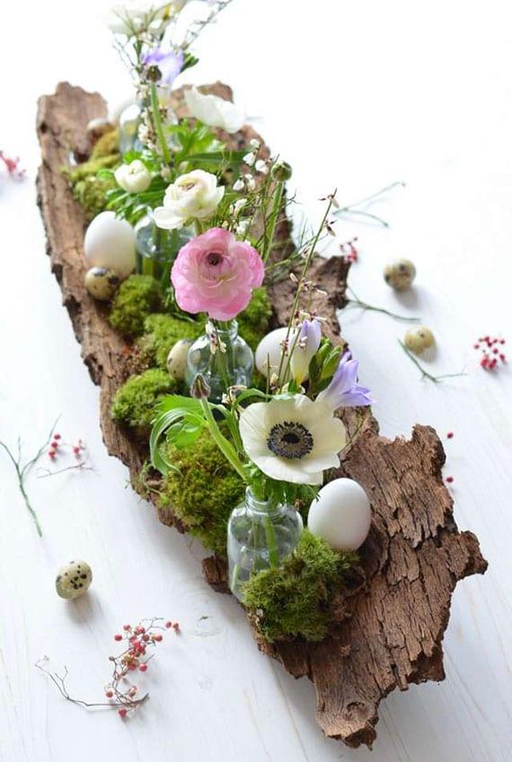 schönes oatergesteck mit moos, frühlingsblumen und ostereiern selber machen auf baumrinde