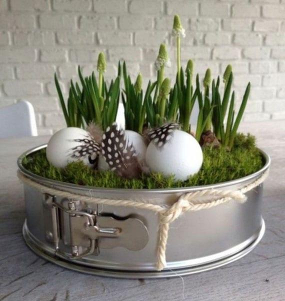 einfache bastelidee für diy osterdeko mit zwerghyazinthen, weißen eiern und feinen federn in einer springform