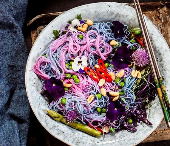 coole rezeptideen für bunte und leckere speisen wie ein teller mit einhorn-glasnudeln, erbsen, ernüssen und essbaren blumen