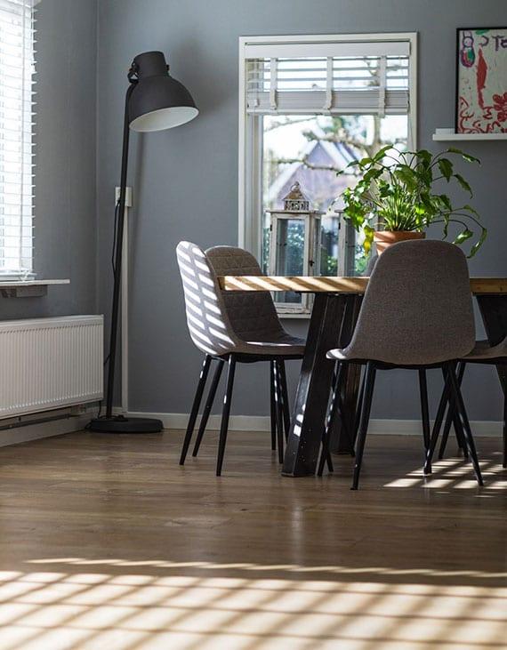 ein esszimmer mit massibholzboden stilvoll einrichten mit vintage esstisch aus massivholz und modernen polsterstühlen in grau