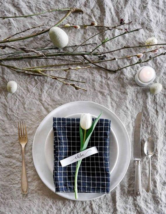 festlichen tisch decken zu ostern mit lainen tischdeko in grau, weißer tulpe mit tischkarte auf blauer serviette im teller und weidenzweigen als tischdeko