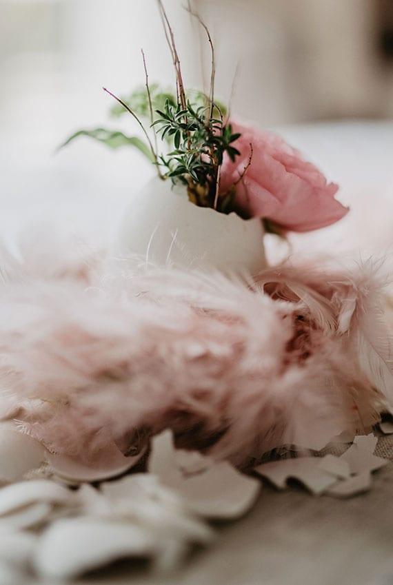 coole ostern tischdekoration mit blüten in weißer eierschale, mini-osternest aus rosafarbigen federn und gebrochenen eierschalen