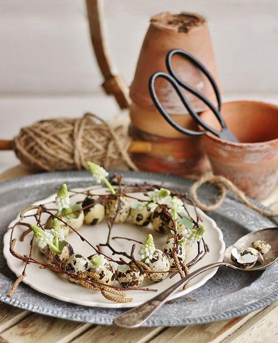 festlicher tisch fürs oaterfest rustikal eindecken mit vintage tellern und kleinem diy osterkranz aus wachteleiern, weißen Zwerghyazinthen und weidenzweigen