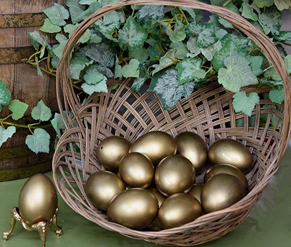 schöne gartendeko zu ostern mit gold gefärbten ostereiern in weidenkorb unter eine grüne kletterpflanze
