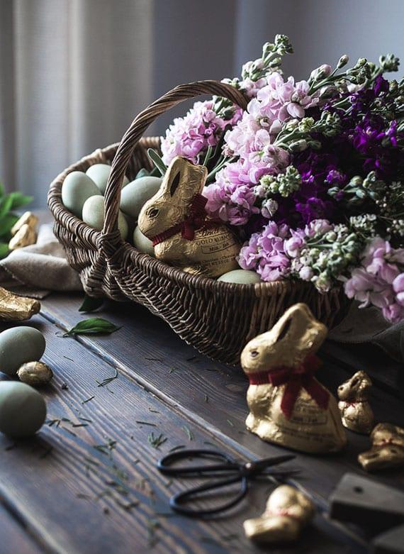 stilvolle osterdekoration mit einem osterkorb voll mit frühlingsblumen, ostereiern in pastellfarben und leckeren schokoladenhasen