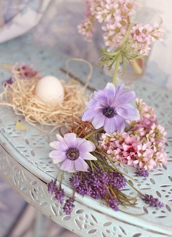 blumendeko idee zu ostern mit osternest und frischen blumen in rosa und lila