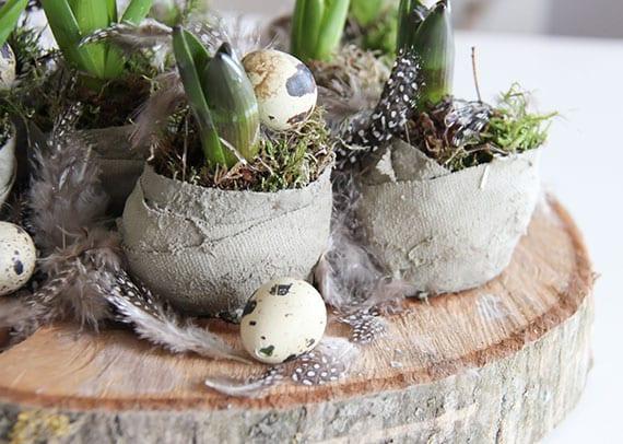 coole bastelidee für attraktive tischdeko zu ostern mit blumenzwiebeln in zementschalen mit moss, wachteleiern und federn
