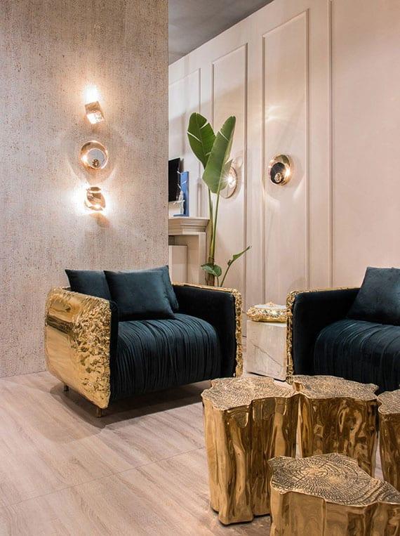 luxus interieur design in hellen farbtänen und mit extravaganten designer möbeln in gold_modernes wohnzimmer mit betonwand, parkettboden, sofa und sessel in grün und gold und originellem couchtisch-set aus metall