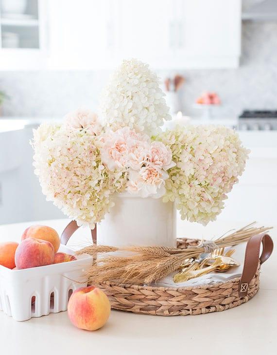 Esstisch in eine einladende Tafel durch schlichte Herbstdeko mit hortensien,pfirsichen und weizenstängeln verwandeln