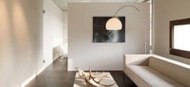 kleines wohnzimmer schlicht und modern einrichten mit mobiliar in weiß und glastrennwand zum schlafbereich und natürlicher tischdeko