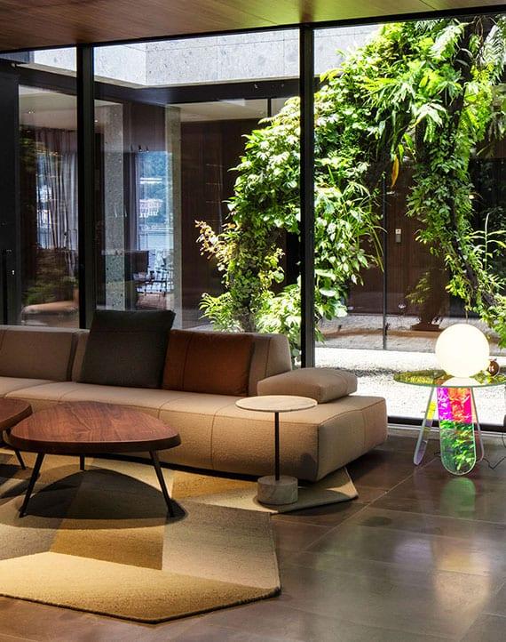 schöne und attraktive wohnzimmer idee mit panoramafenstern zum innenhof, designer sofa in beige, modernen holzkaffeetischen und originellem teppich in geometrieform