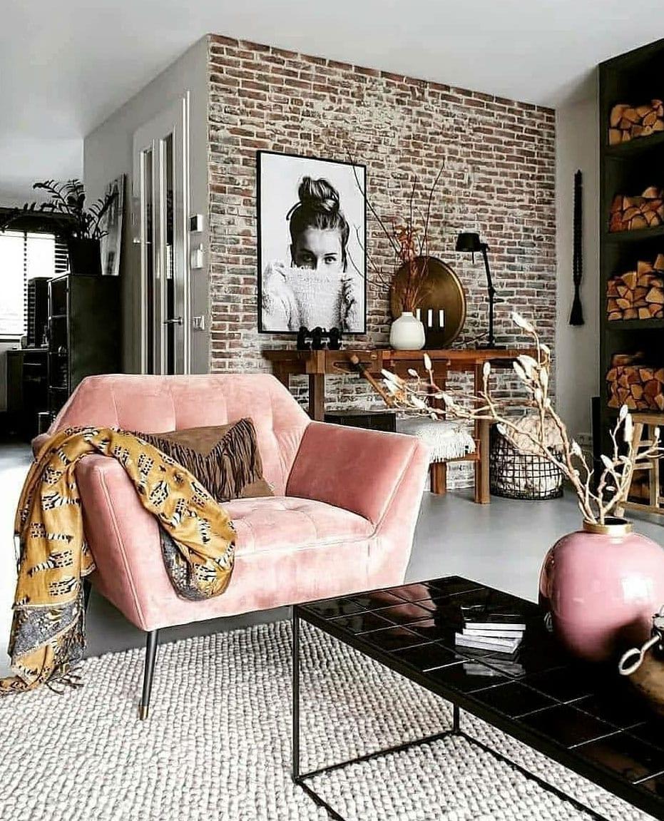 wohnliches und modernes wohnzimmer mit sessel in pink einrichten_attraktive wohnzimmer idee mit ziegelwand, vintage sideboard aus holz, wohnwand mit kamin und feuerholznische