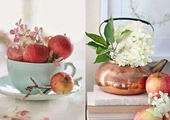 raffinierte Frühlingsdeko mit hortensienblüten und äpfeln in einer kaffeetase und edle tischdeko mit weißen hortensienblüten in messing-teekane