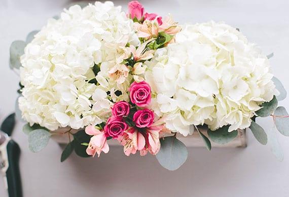 elegante tischdekoration mit weißen Hortensien, Eukalyptus, rosafarbigen Inkalilien und rosen in pink