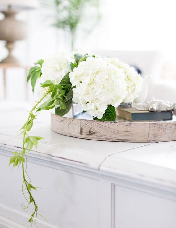 elegante blumige tischdeko mit einem buch, weißer hortensie und jungfernrebe in einer runder holzschale