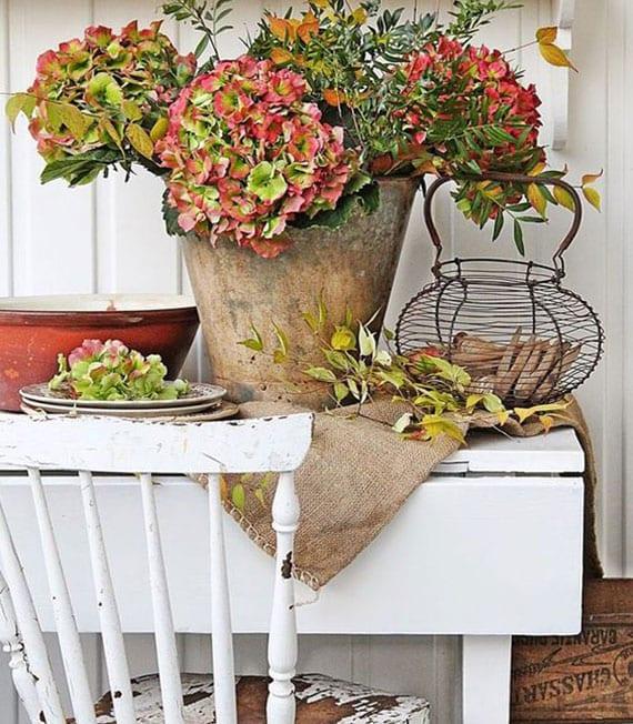 rustikale blumendekoration im herbst zaubern mit hortensien und herbstzweigen