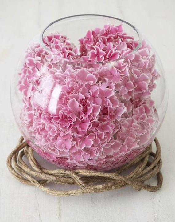 coole tischdeko mit rosafarbigen hortensienbällen in kugel-glasvase und weinstock