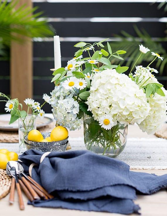 coole outdoor tischdekoration mit zitronen, weißen hortensien,Kamillen und dunkelblauen servietten