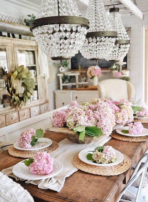 tisch rustikal eindecken blumig dekorieren mit rosafarbigen hortensiendolden in einer holzschale und in weißen porzellantellern