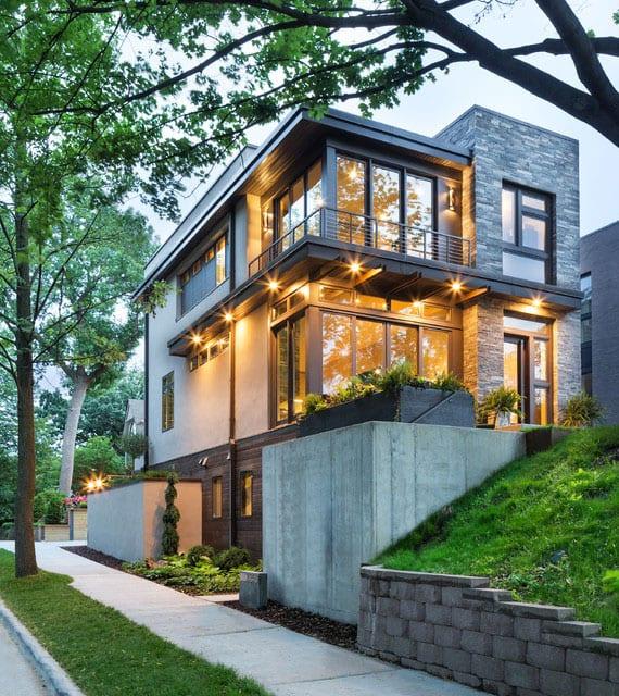 ideen für moderne hausfassade in weiß und grau mit naturstein-wandverkleidung, akzentuierender gebäudebeleuchtung und eckferglasung