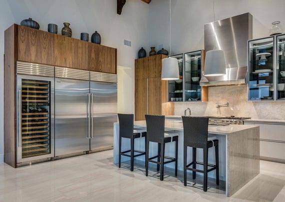 moderne küche mit kochinsel und theke, küchenmöbel in holzoptik und modernen einbau-gefriergeräte inox