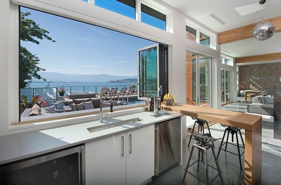modernes küchendesign mit panoramafenster entlabg der arbeitsplatte, frühstücksbar als trennelement zum wohnzummer und unterbau-kühl-und gefrierschrank