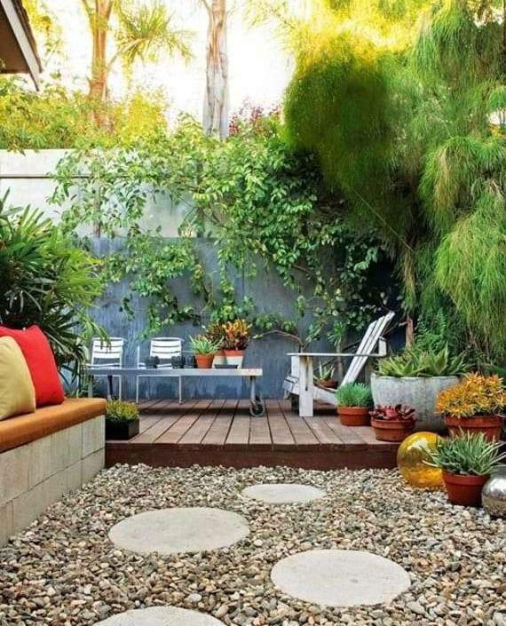 gartendesign idee für hofgarten mit holzterrasse, kletterpflanzen und kiesgarten mit runden trittsteinen und eingemaerter sitzbank