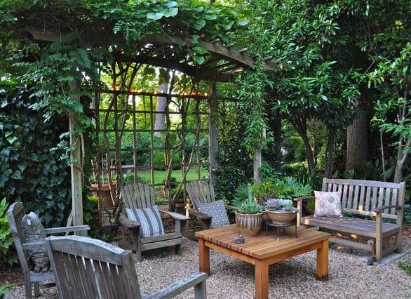 gestaltungsiedee für geheimgarten mit einladender sitzecke unter holzlaube mit gitter für kletterpflanzen, holzgartenmöbeln und kiesboden