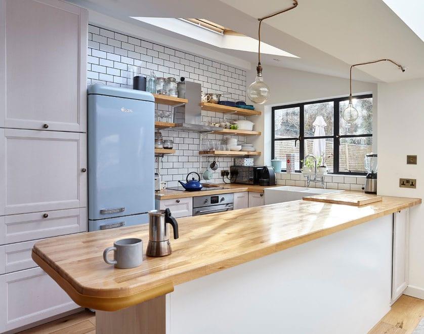 attraktive einrichtungsidee für kleine küchen im vintage stil mit retro-kühlschrank in hellblau, metro wandfliesen weiß, holzwandregalen und frühstücksbar