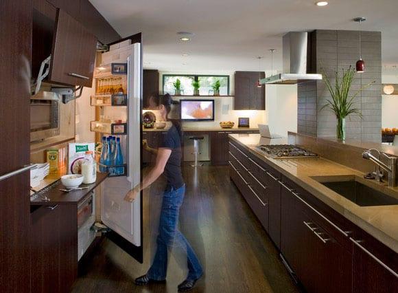 moderne offene küche in holzoptik mit einbau-elektrogeräten und großer kochinsel
