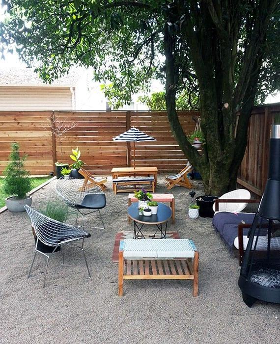 garten stilvoll gestalten mit kiesbereich für einladende sitzecke im schatten mit gartenkamin, sofa und kübelpflanzen