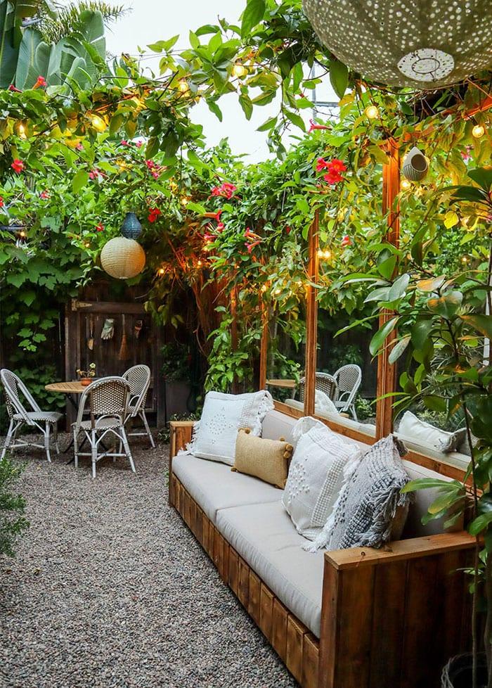 kleinen hofgarten in traumhaften rückzugsort verwandeln mittels Kies, begrünter gartenwand mit kletterpfalnzen, wanddeko mit spiegeln in holzrahmen und diy gartensofa aus paletten