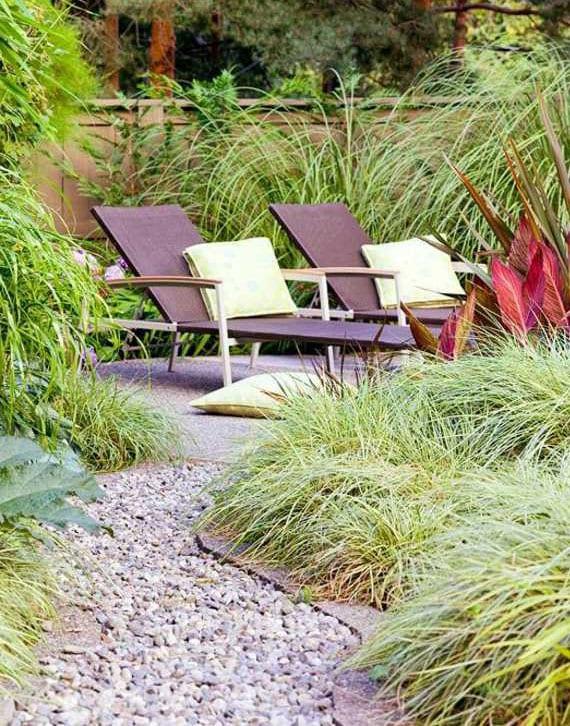 gartenweg mit kies und pflastersteinen für einen naturgarten mit sonnenterrasse zwischen ziergräsern