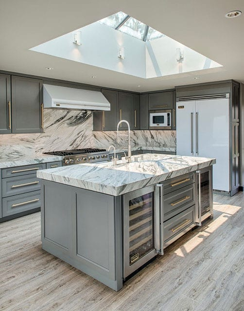 luxus küchengestaltung im klassischen stil mit oberlicht über kochinsel, grauen küchenfronten, marmor-arbeitsplatte und spritzschutzwand, modernem einbaukühlschrank in weiß