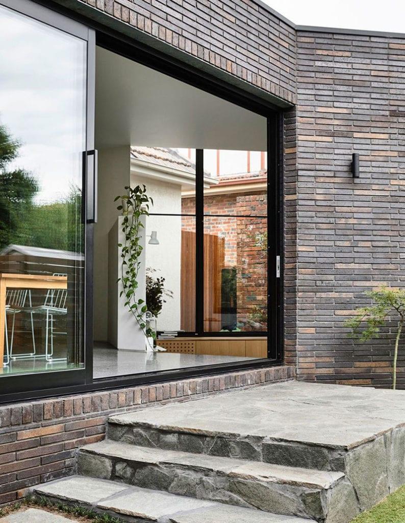 eingeschösiges haus mit formschöner hausfassade aus dunklen klinkern, grosformatiger schiebetür und natursteintreppe zum garten