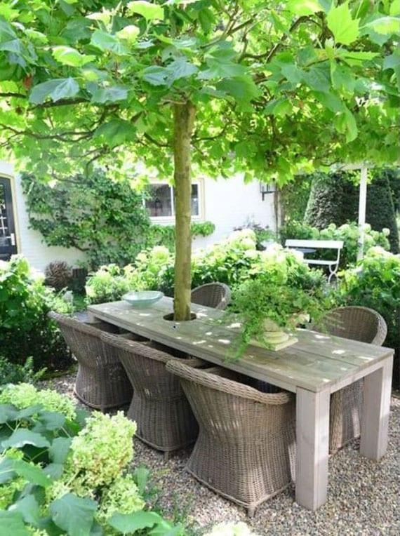 coole garten ideen für eine romantische und einladende gartengestaltung mit angehenmen sitzplatz unter einem natürlichen schattenspender