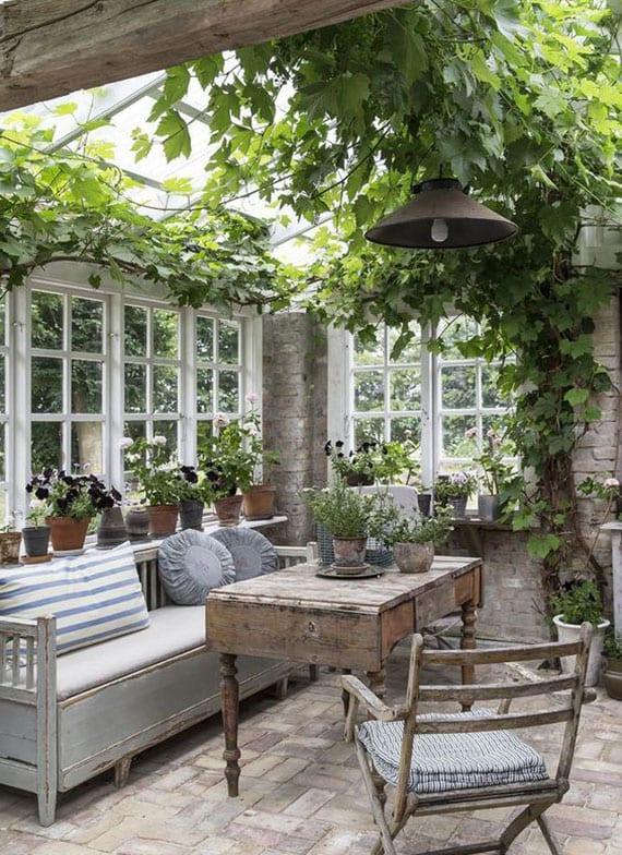 romantischen und geheimvollen sitzplatz im garten einrichten mit vintage-möbeln aus holz, ziegelwänden, sprossenfenstern und weinreben
