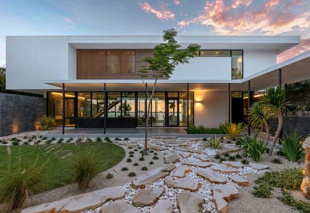 minimalistisches zweistockiges haus in weiß mit flachdach und panoramaverglasung zum steingarten und see