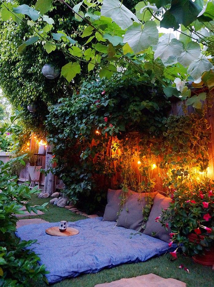 eine traumhafte entspannungsecke im garten gestalten mit lichterkette und matrattratze unter einem grünnen dach aus kletterpflanzen