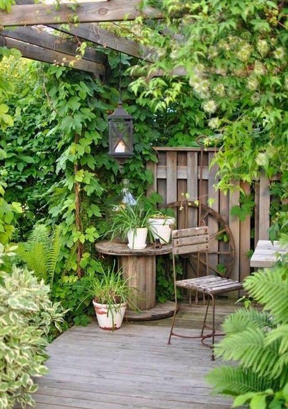 geheime sitzecke im garten gestalten mit begrünter gartenzaun, holzterrasse mit holzpergola und vielen kletterpflanzen