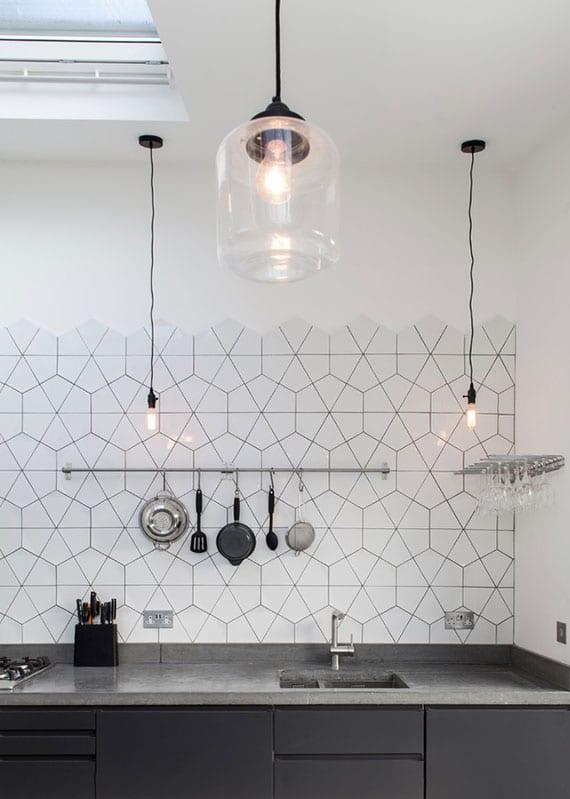 minimalistisches küchendesign in schwarz und weiß mit spritzschutz aus weißen hexagonalen wandfliesen, schwarzen küchenschränken mit betonarbeitsplatte und designer pendelleuchten