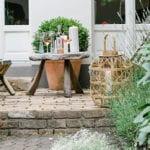 romantische sitzecke im garten einrichten mit holzklappstühlen, holzlaternen und rundem dreibein tisch