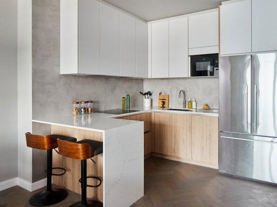 kleine küche im wohnzimmer stilvoll und schlicht gestalten in weiß und holz, mit kleinem esstheke und microzement küchenwand