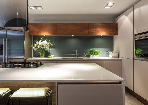 schöne gestaltungsidee für offene küche in weiß mit kochinsel, gasherd und glas-spritzschutz in grün