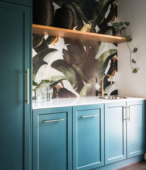 coole idee für edle und effektvolle küchengestaltung mit küchenschränken in blau, holzwandregal und abwaschbarer Kunststofftapete mit floral muster als spritzschutz