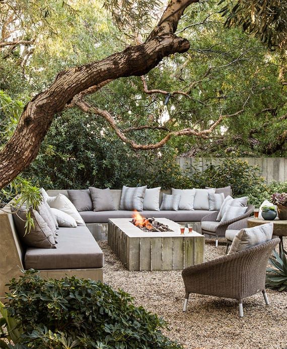 harmonische gartengestaltung einer sitzecke aus beton mit grauen polstern und dekokkisen,diy feuerstelle im kiesboden