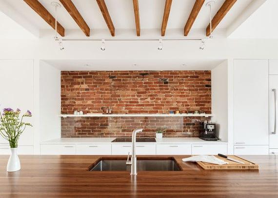 moderne küche in weiß mit kochinsel in holz und küchenrückwand aus ziegeln mit spritzschutz aus transparentem glas mit weißem wandregal