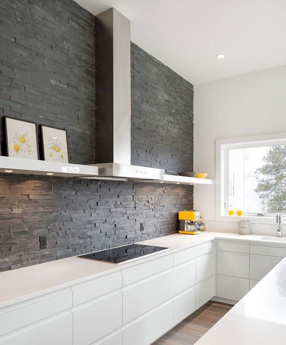 moderne und individulelle küchengestaltung in weiß mit küchenrückwand aus grauen naturstein fliesen
