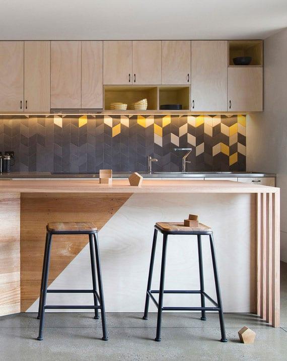 kleine moderne küche in holz mit attraktivem spritzschutz aus geometrischen fliesen in grau und gelb, kochinsel mit esstheke aus holz und vintage-barhockern