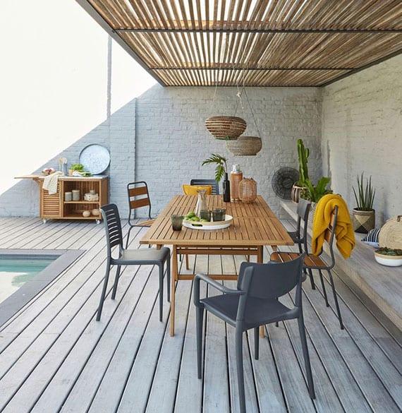 moderne gestaltung einer sitzecke im freien unter holzüberdachung mit weißen ziegelwänden, sitzbank aus beton, holzesstisch und pool